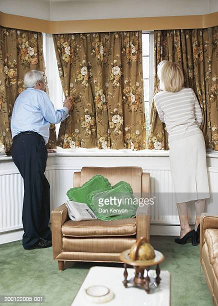 Senior couple at window, peering around curtains, rear view
