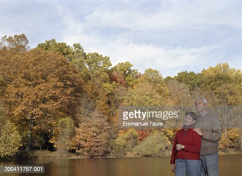 Senior couple beside pond looking upwards, autumn : Stock Photo