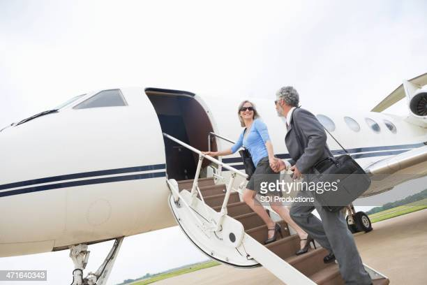 Senior couple boarding luxurious private jet