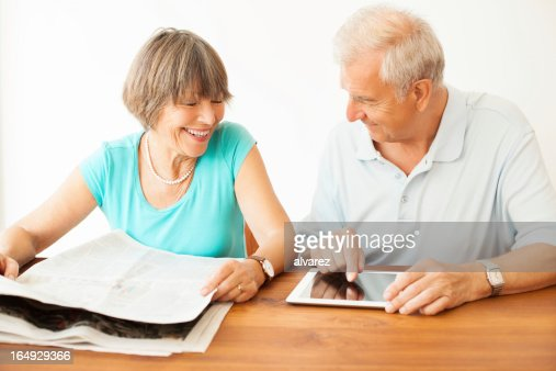 Senior couple both with newspaper and digital tablet