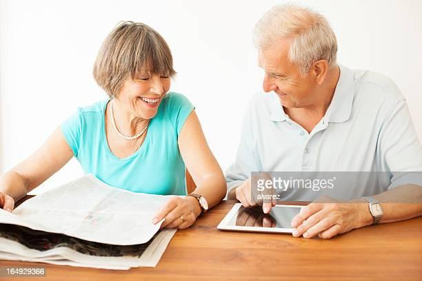 Altes Paar beide mit Zeitung und digital tablet