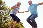 Senior Couple Bouncing On Trampoline In Garden Laughing