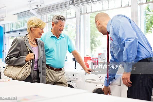 Senior couple buying a washing machine