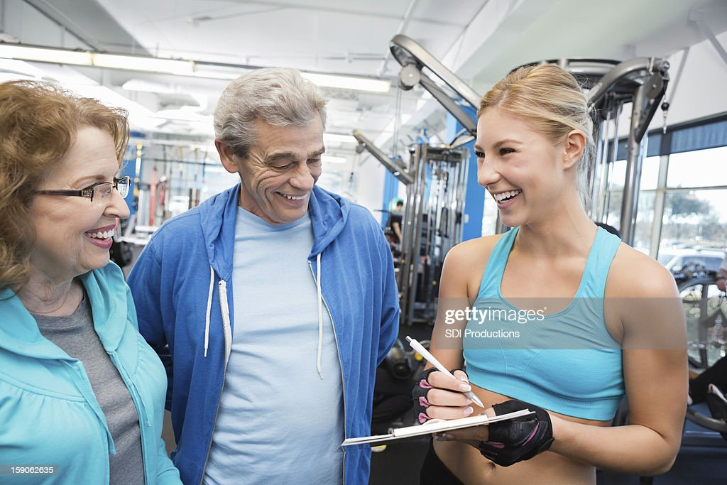 Senior couple buying gym membership from athletic personal trainer : Stock Photo
