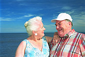 Senior couple by sea, smiling at one another, close-up