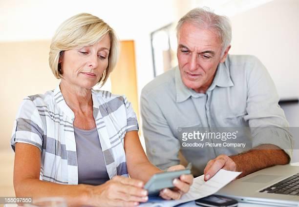 Senior couple calculating their financial expenses