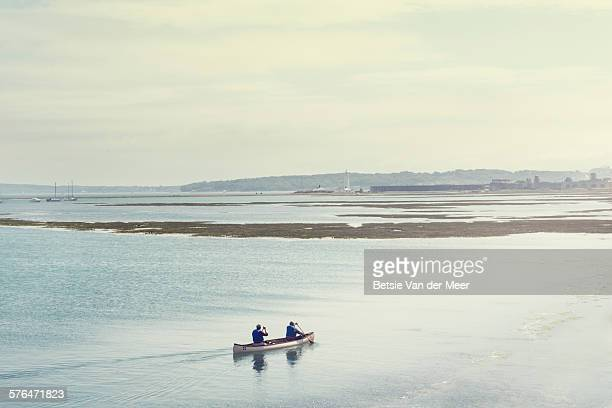 Senior couple canoeing at sea, land in distance.