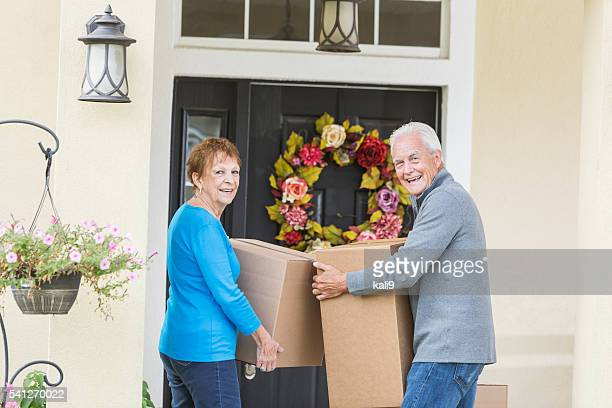 Senior couple carrying boxes to front door of house