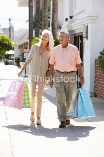 Senior couple carrying shopping bags stock photo thinkstock