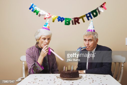 Senior couple celebrating birthday at dining room table : Stock Photo