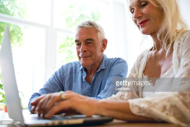 Senior couple checking bills at home in the morning