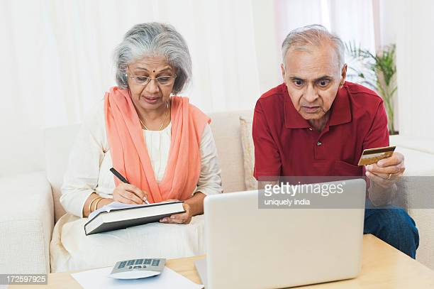 Senior couple checking bills on a laptop