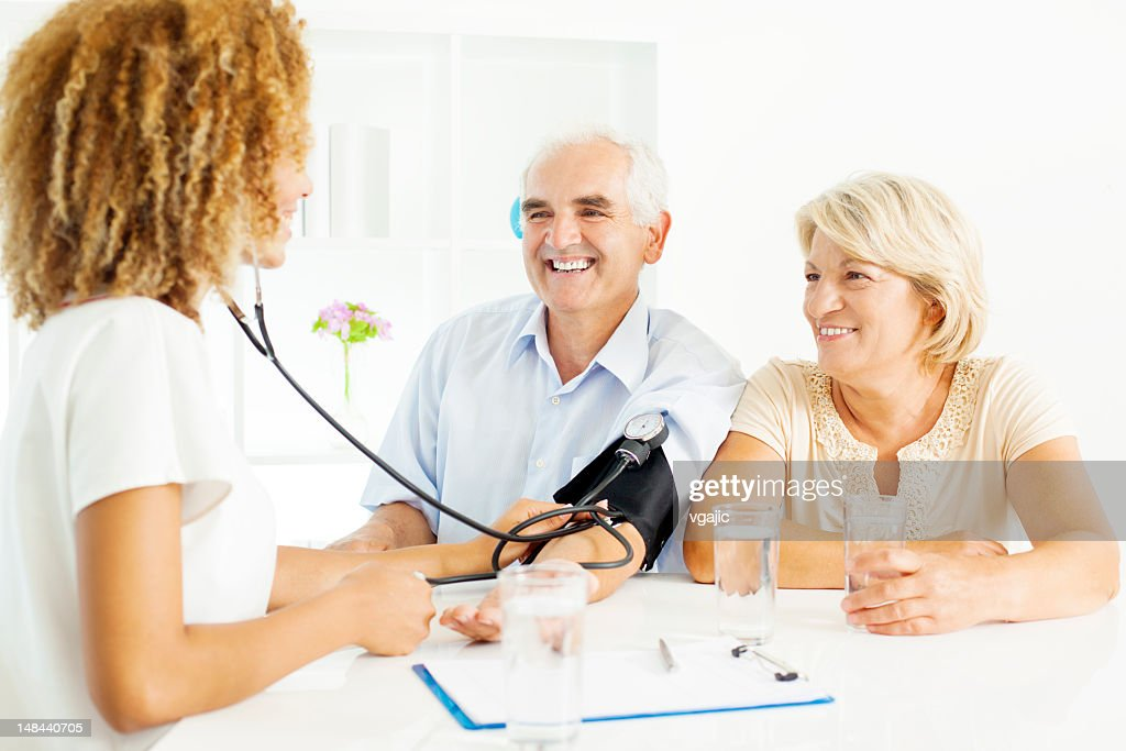 Senior couple Checking Blood Pressure at doctors office. : Stock Photo
