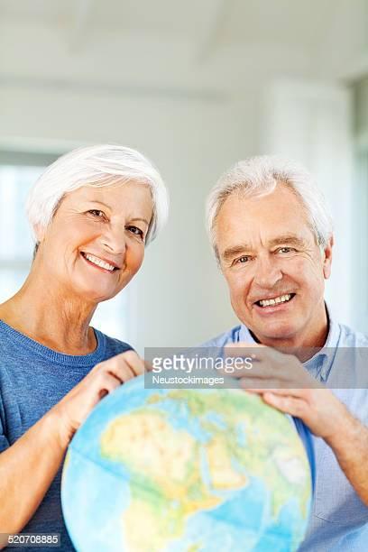 Altes Paar Auswahl Reiseziel auf der Welt zu Hause fühlen