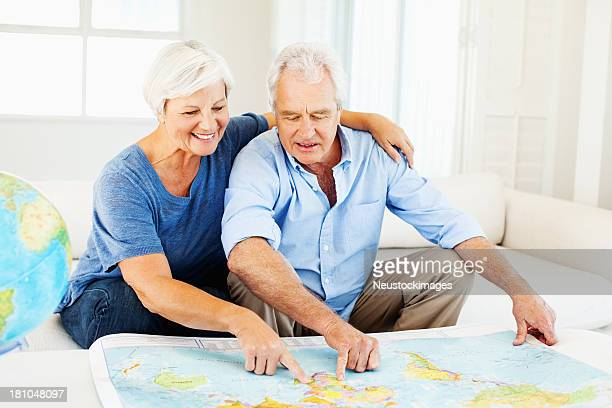 Senior Couple Choosing Travel Destination On Map