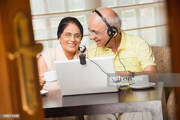 Senior couple communicating on laptop, man wearing headset