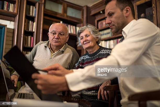 Senior couple cooperating on a meeting with their consultant.
