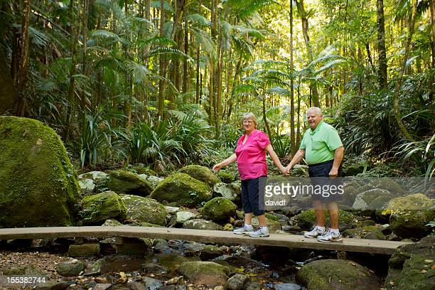 Senior Couple Crossing a Rainforest Stream