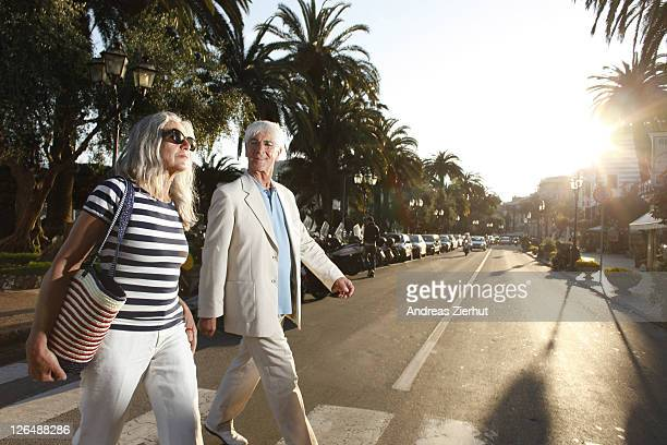 Senior couple crossing road, Italy