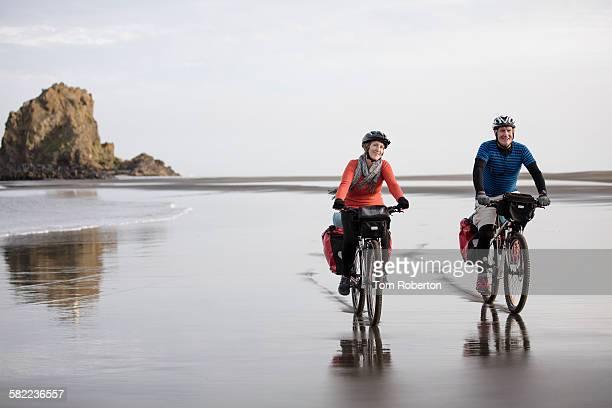 Senior couple cycling along shoreline of beach