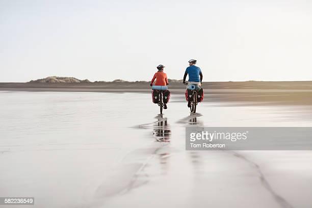 Senior couple cycling on deserted beach