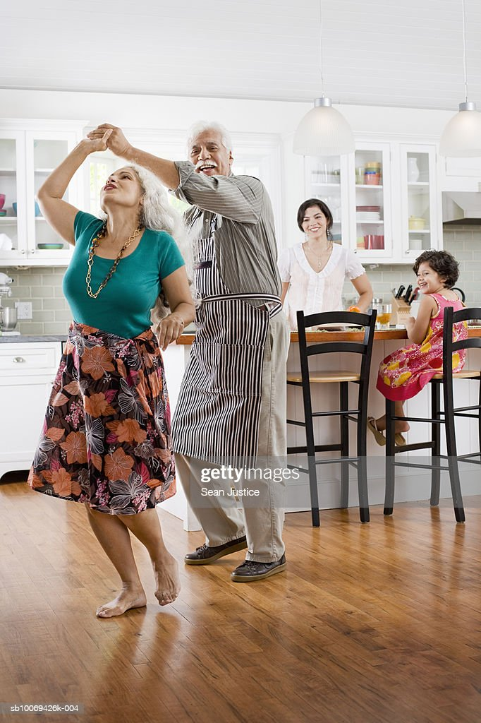 Senior couple dancing in kitchen, granddaughter with mother watching : Stock Photo
