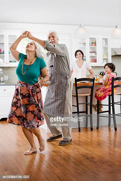 Senior couple dancing in kitchen, granddaughter with mother watching