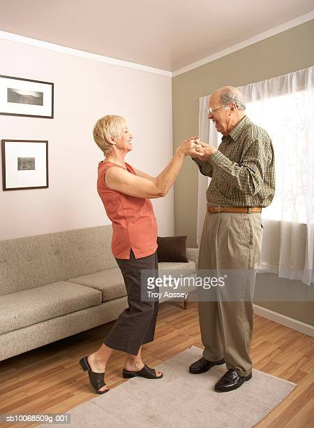 Senior couple dancing in living room, holding hands, side view