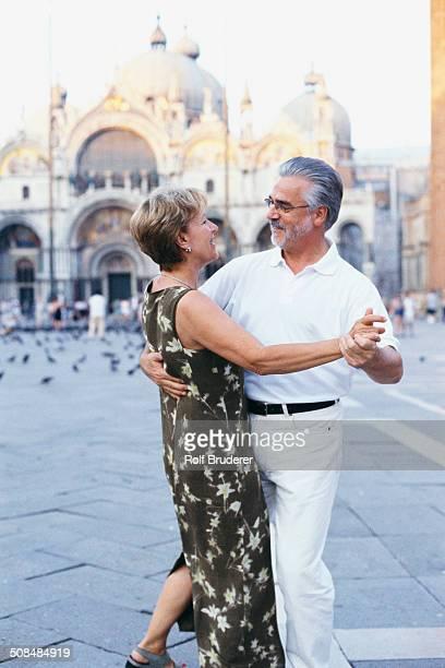 Senior couple dancing in St. Mark's Square, Venice, Veneto, Italy