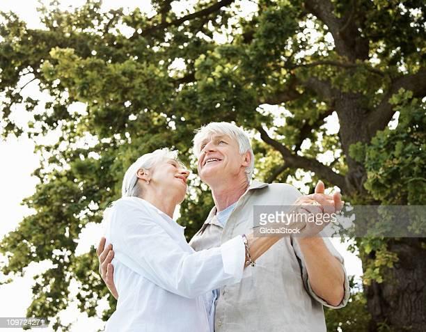Altes Paar Tanzen zusammen unter Baum