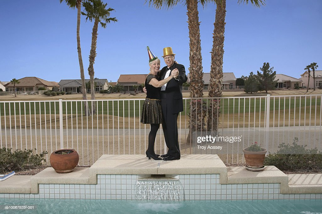 Senior couple dancing with party favors at pool on New Years Eve : Stock Photo