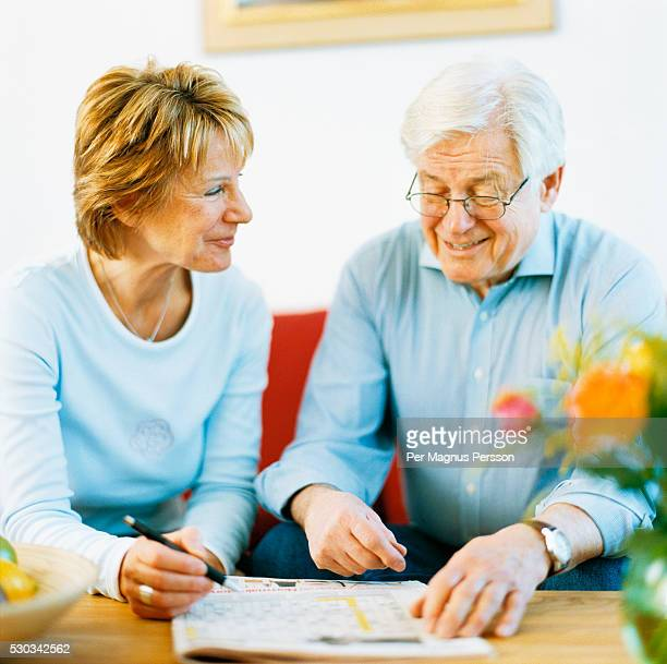 Senior couple doing crossword puzzle in living room