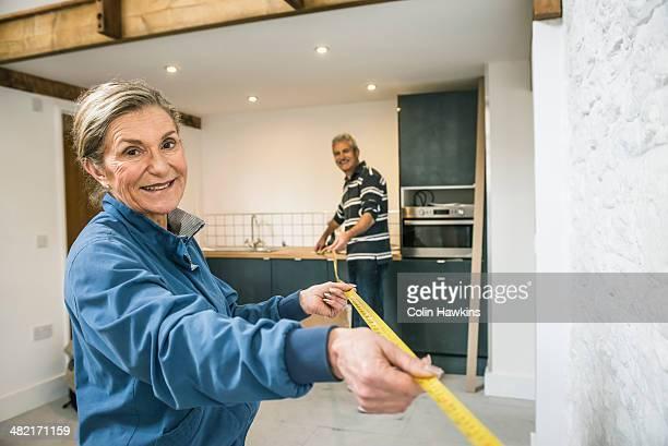 Senior couple doing DIY, using measuring tape
