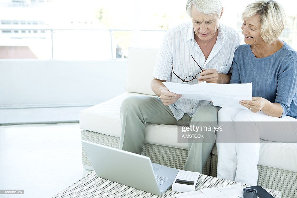 Senior couple at home doing paperwork : Stock Photo