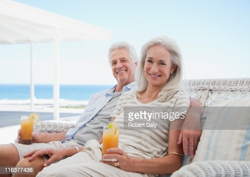Senior couple drinking cocktails on beach patio