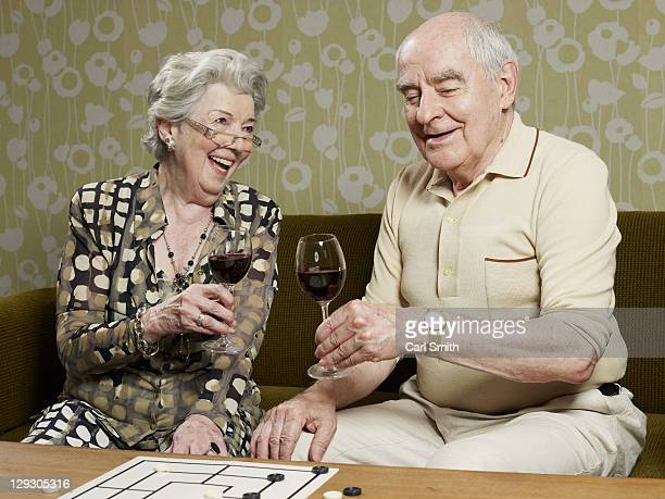 Senior couple drinking red wine make a toast on the couch