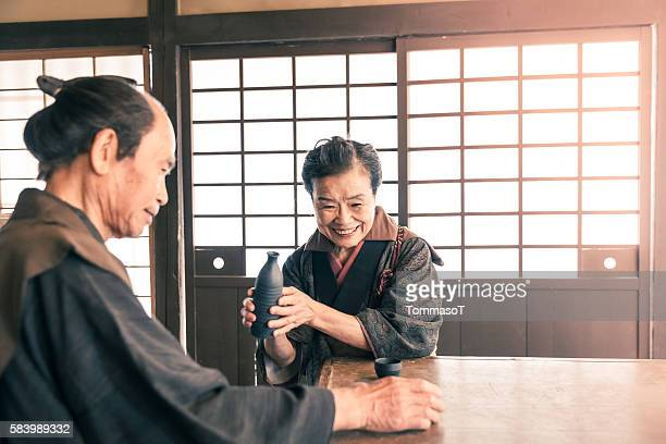 Senior couple drinking sake in front of shoji doors