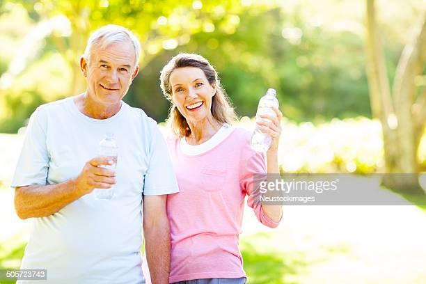 Coppia Senior bere acqua dopo l'allenamento