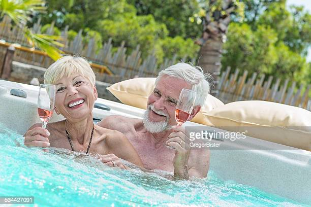 Senior Couple Drinking Wine in Jacuzzi