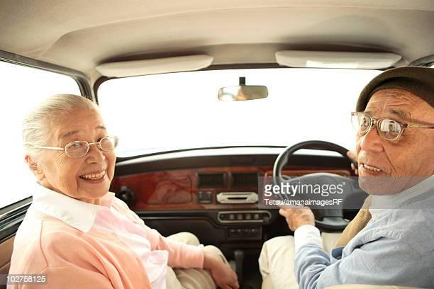 Senior couple driving a car