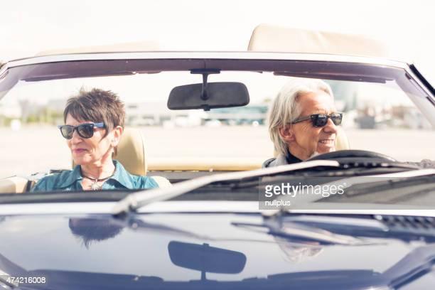 Coppia senior guida di una cabriolet auto d'epoca