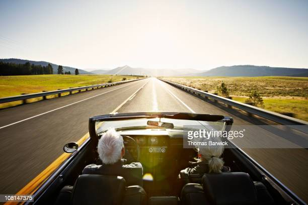 Senior couple driving convertible car at sunrise