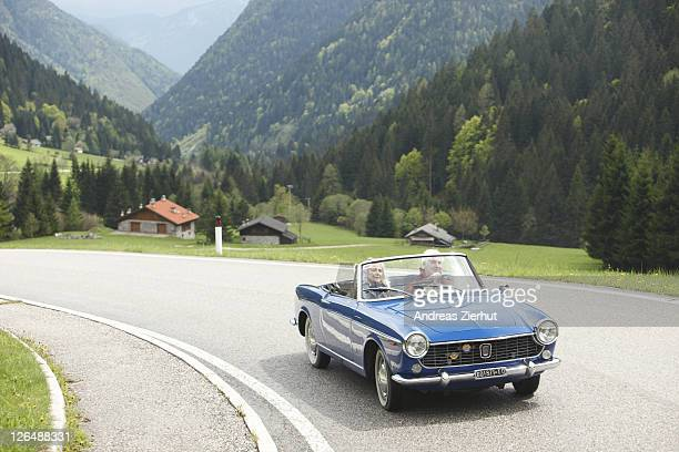 Senior couple driving convertible on country road, Italy