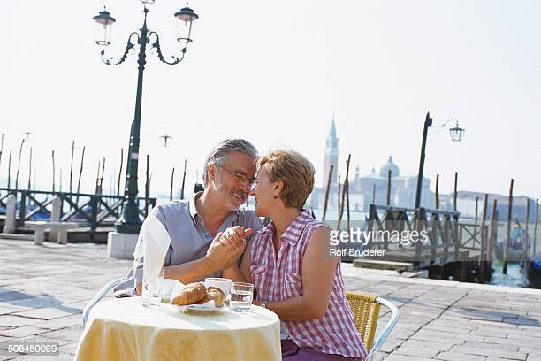 Senior couple eating at sidewalk cafe, Venice, Veneto, Italy