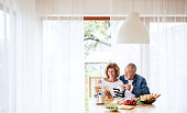 Senior couple eating breakfast at home. An old man and woman sitting at the table, relaxing.