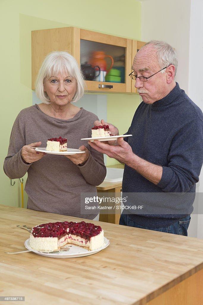 Senior couple eating cake in kitchen