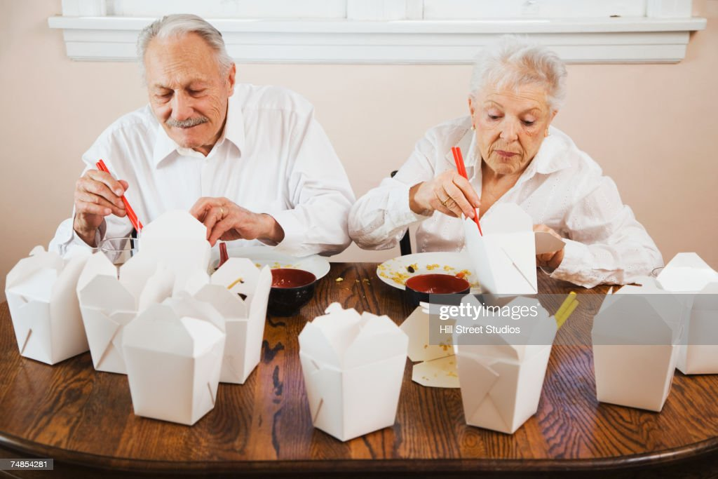 Senior couple eating Chinese takeout food