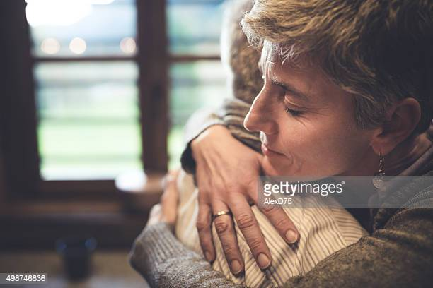 Senior couple embrace in kitchen