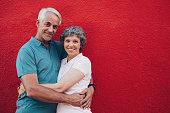 Portrait of loving middle aged man and woman standing together against red background. Senior couple embracing against red wall with copy space.