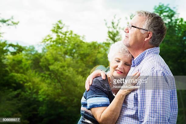 Senior couple embracing by bay window
